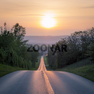 Road leads into sunset in Europe