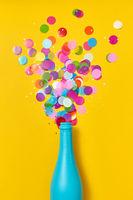 Multicolored confetti as a bubble foam above open champagne bottle.