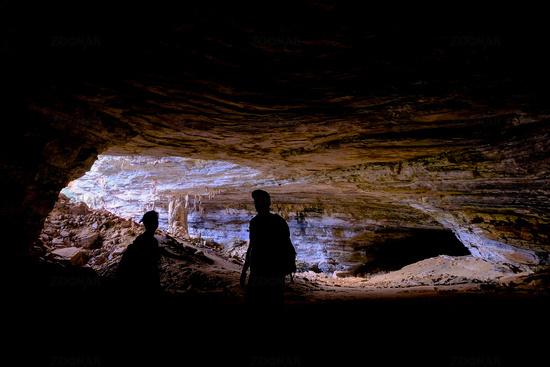Two unrecognizable tourists at the entrance of Gruta Da Lapa Doce, cave in Iraquara, Chapada Diamantina, Bahia, Brazil
