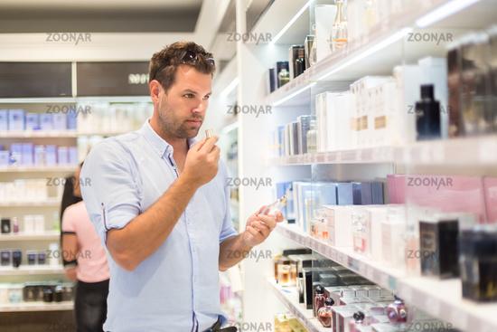 Elegant blond young woman choosing perfume in retail store.