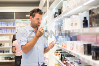 Elegant blond young woman choosing perfume in retail store.
