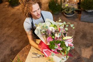Junger Florist verpackt bunten Blumenstrauß