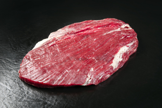 Raw dry aged wagyu flank steak as closeup on black background with copy space