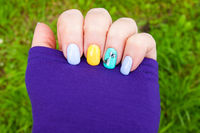 Manicure - gel polish color in bright summer tones, butterflies are pasted on one nail - photo.