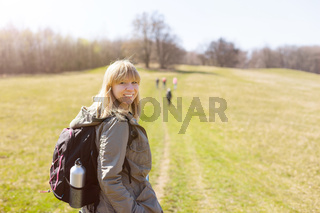 Woman is hiking and trekking outside on a hill. Tourism, vacation and fitness activity concept.