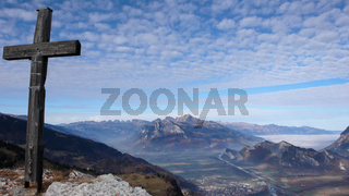 mountain landscape in Switzerland with a view of the Rhine Valley and summit cross in front