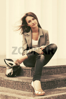 Happy young fashion woman in grey blazer and dark blue jeans sitting on steps