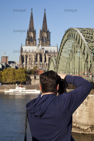 A man photographs Cologne Cathedral with the Hohenzollern Bridge, Cologne, Germany, Europe