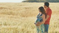 Pregnant woman and her husband hugging on the tummy together in nature outdoor on field.