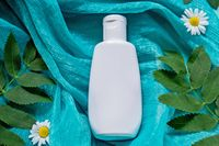 White bottle with cosmetic on green silk cloth background with field flowers and leaves. The concept of summer and idea for advertisement of liquid soap, cream or shampoo. Flatlay.