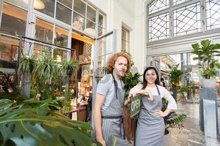 Zwei Floristen mit open Schild vor Gartencenter