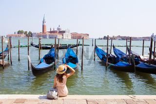 Beautiful sunny Venice-girl sitting on the pier, near the gondola