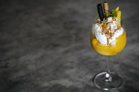 mango and passion fruit tropical ice cream sundae in glass