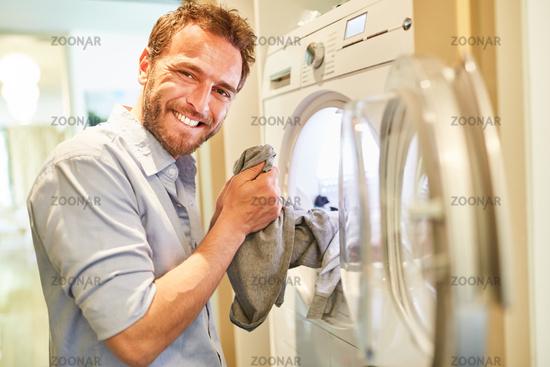Hausmann mit Wäsche am Wäschetrockner
