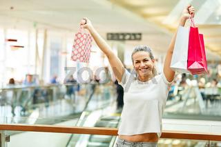 Junge Frau mit Einkaufstüten jubelt