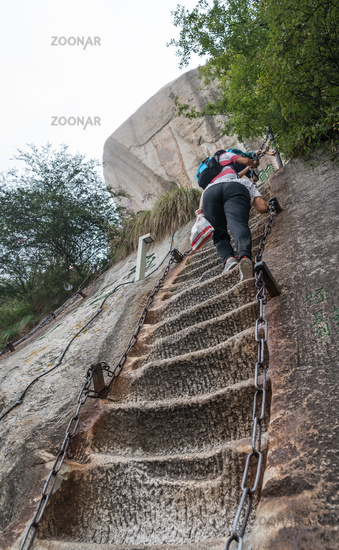 Climber tackling steep stone stairs on Huashan mountain