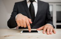 Male human wear formal working clothes presenting presentation of high technology smartphone device. Man dressed in work suit plus tie showing small mobile hi tech phone