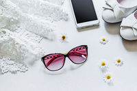Travel concept summer background, sunglasses, flowers, mobile phone. Overhead view of Traveler's accessories. Essential vacation items, love story, go to see the world. Flat lay