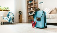 Travel suitcase standing on floor in the room.