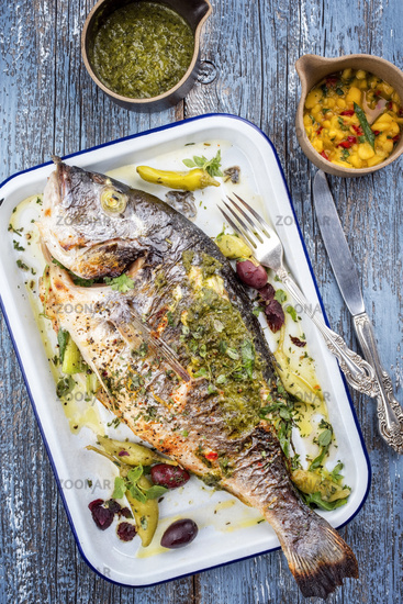 Fresh barbecue gilthead seabream with mango chutney and chimichurri as top view in a white skillet
