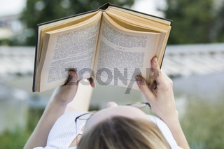 Young woman reading an old book lying outdoors at summer day