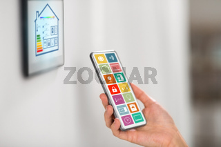 hand with smart home icons on smartphone screen