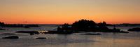 Bright orange morning sky over small islands near the shore of Lake Vanern.