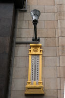 Photo of street design. An electric lamp on one of the buildings above a gilded street thermometer showing the temperature of the air in the street
