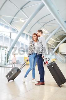 Junges Paar mit Koffern im Flughafen Terminal