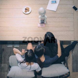 Beijing, China - March 12, 2019: Three Asian Teen Girls Video Chatting on Phone Coffee Table from Above