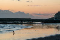 Unidentifiable person with surfboard walking at low tide on Seaford Beach at sunset