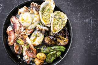 Traditional barbecue seafood platter with herb as top view on a plate with copy space right