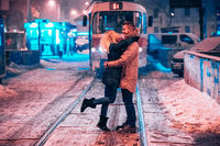 Young adult couple on the snow-covered tram line