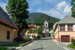 Street Scenario with buildings during main Road and main Parish Church of Village Log pod Mangartom. Bovec, Slovenia, Europe.