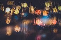 Traffic lights through the window in a rainy night