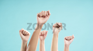 Multiethnic male and female hand raised against a blue background