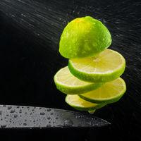Green lemon cut on the fly, water spray.