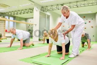 Physiotherapeutin gibt Hilfestellung bei Rückengymnastik