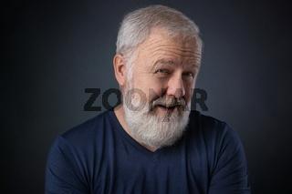 Elderly man with beard looking skeptical