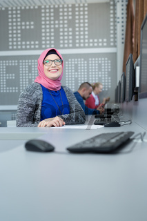 Woman wearing hijab working in her office. Cooperating office space. Sharing office with colleagues.