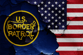 flags of United States Border Patrol and USA painted on cracked wall