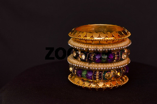 Artificial golden and colored bangles close up on a black background.