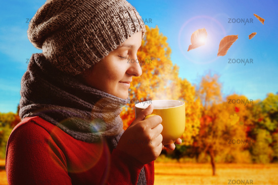 Young woman wearing a woolen scarf and a cap drinking hot tea in front of a autumnal landscape.