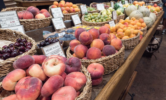 market stand with many different fruit and labels with names and prices in French