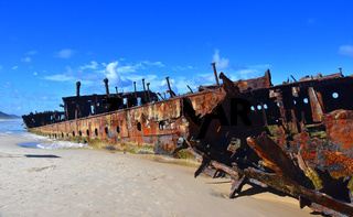 The rusty wreck of the vessel Maheno on the shores of Fraser Island (Queensland, Australia). The antique rusty and damaged boat and corrosion in the ocean sea.