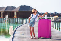 Little adorable girl with big luggage on wooden jetty on her way to water bungalow during summer vacation