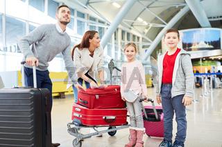 Familie und zwei Kinder mit Gepäck im Terminal