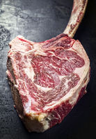 Traditional raw dry aged wagyu tomahawk steak as closeup on an old rustic board