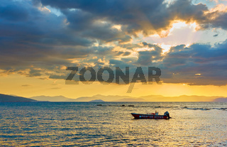 Sea with boat at sunset