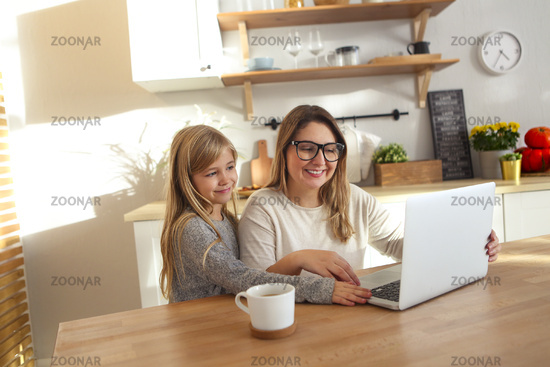 Mother with little girl using laptop in the kitchen
